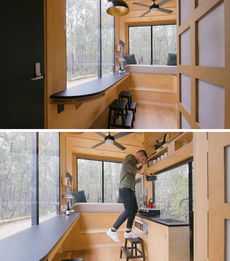In the kitchen of this modern tiny house, there's everything you need from a gas stove to a small fridge. Opposite the kitchen is a breakfast bar, whose stools double as stairs to reach the open shelving in the kitchen. #TinyHouse #TinyHome #BreakfastBar #SmallKitchen