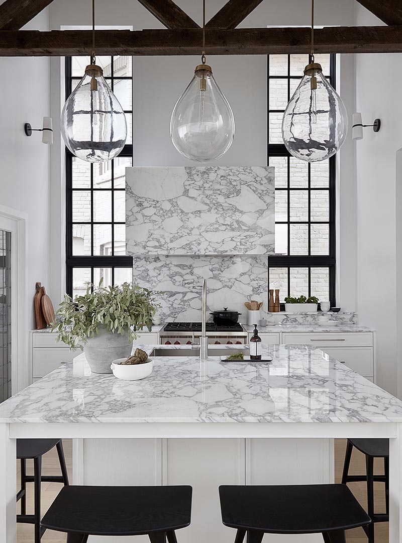 By having a square kitchen island with a white and marble finish, the designers of this kitchen were able to include four spaces for seating in the form of counter stools, which is ideal if you're entertaining and want to interact with the person cooking, or if you need a spot to have a quick bite to eat. #SquareIsland #SquareKitchenIsland #KitchenDesign #KitchenIsland #IslandWithSeating