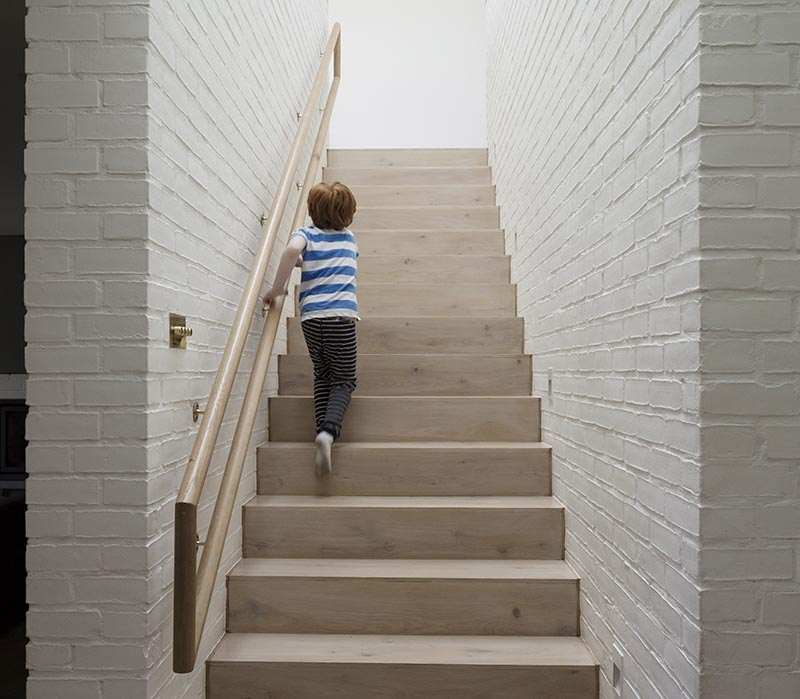 Architecture firm Peter Legge Associates completed a house in Dublin, Ireland, and as part of the design of the stairs, they included a wood handrail that can be used by both adults and children. #StairDesign #HandrailDesign #MultiHeightHandrail