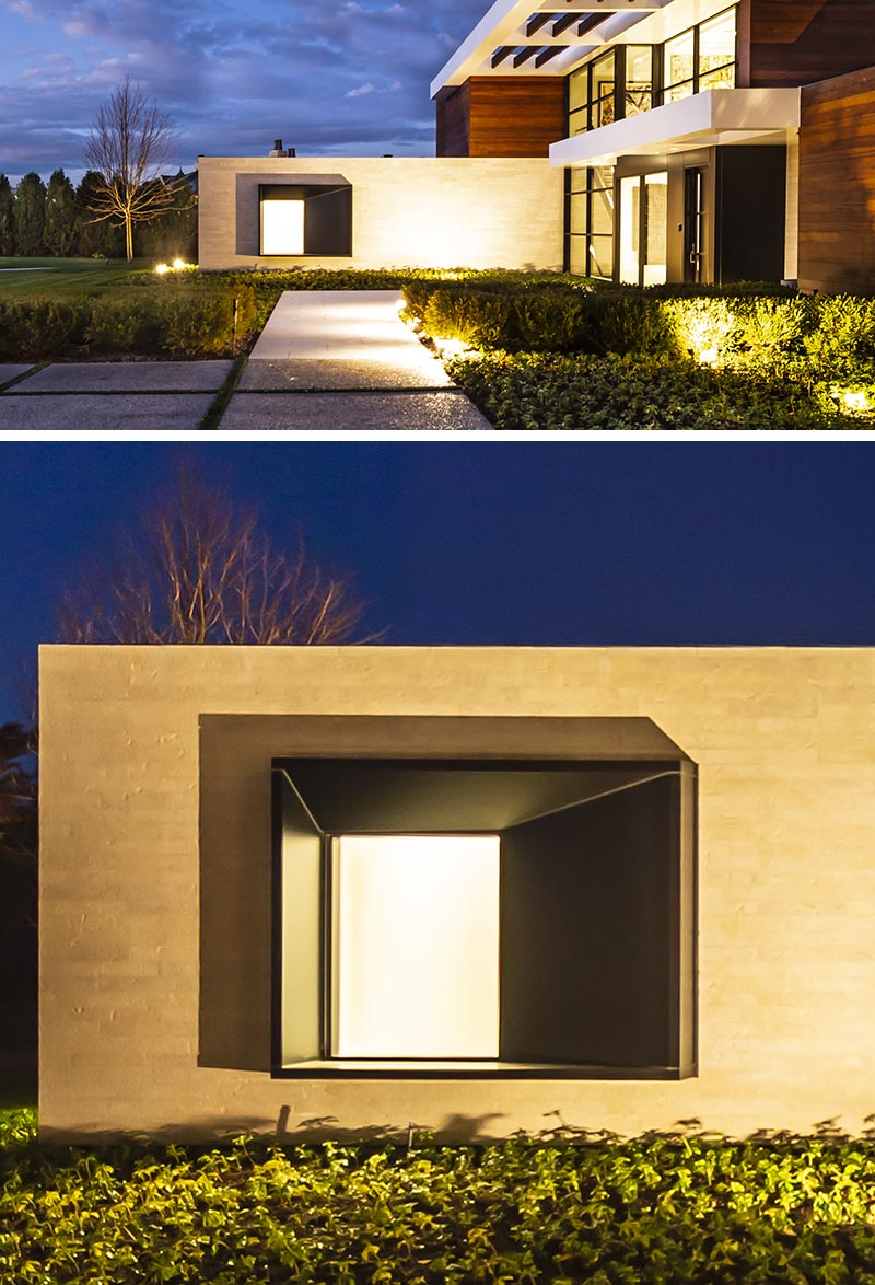 The oversized black steel-clad window frame intentionally juts from the stone entry wall of this modern house, and with its design, it casts a variety of shadows throughout the day, depending on the sunlight or the light coming from within the house. #ProtrudingWindow #WindowDesign #ModernArchitecture #ModernHouse