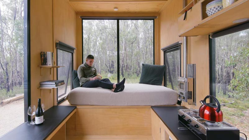 At one end of this modern tiny house is a day bed that's been elevated to create a sense of separation from the breakfast bar and kitchen. #DayBed #TinyHouse #TinyHome