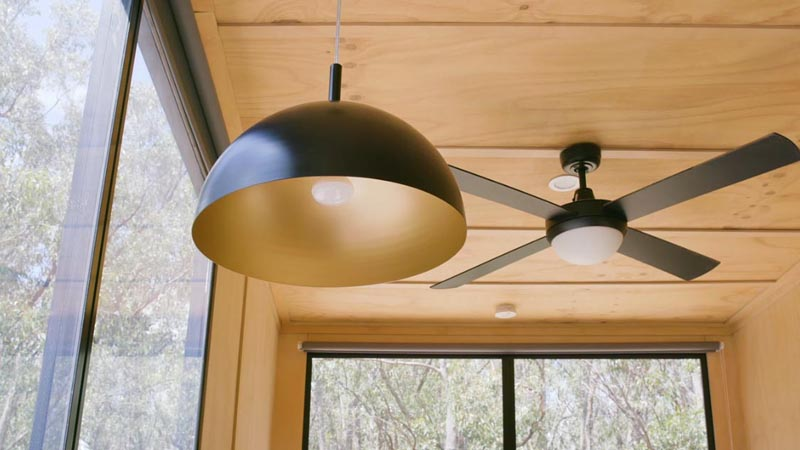 Black accents throughout this modern tiny home, like switches, window frames, and lighting, create a strong contrast to the light wood interior. #TinyHouse #TinyHome #Lighting #Fan