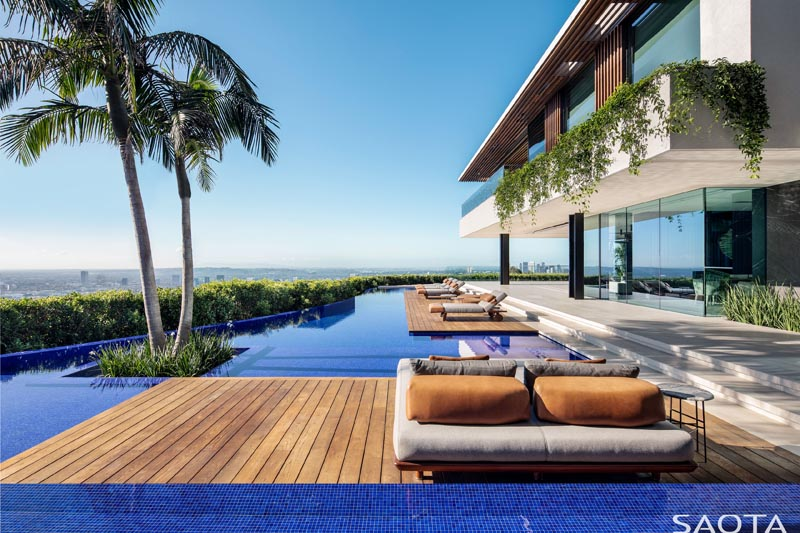 The multiple wooden decks, which step down from the main living areas of the interior, are ideal for relaxing by the pool and have enough room for sun lounges, day beds, side tables, and ottomans. #SwimmingPool #PoolDeck #Deck #Architecture #PoolDesign