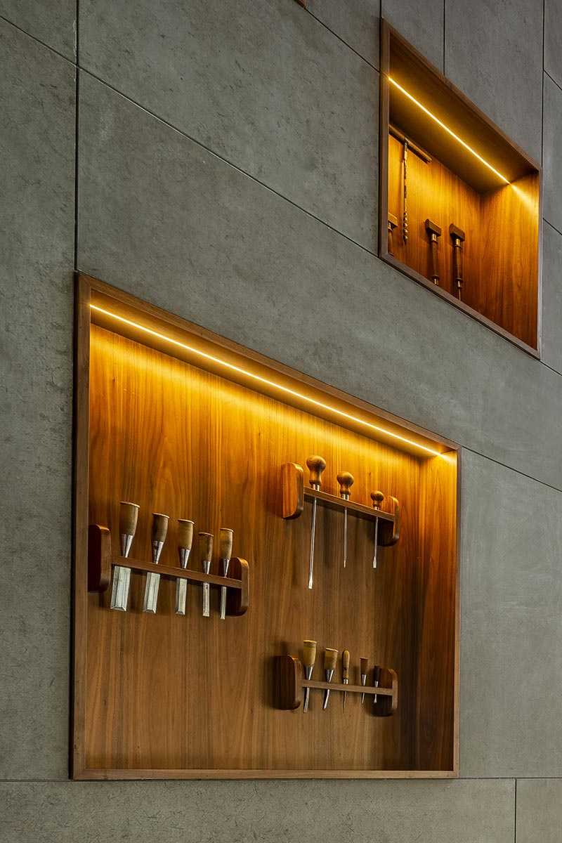 This large and open lobby features a wall with wood-lined built-in shelving, that uses hidden lighting to highlight the woodworking tools on display. #WoodLinedShelves #BuiltInShelving #ShelvingIdea #ShelfLighting #HiddenLighting