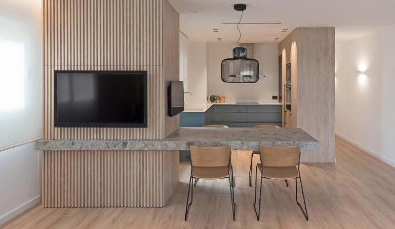 A Cantilevered Dining Table Separates The Kitchen And Living Room In This Apartment
