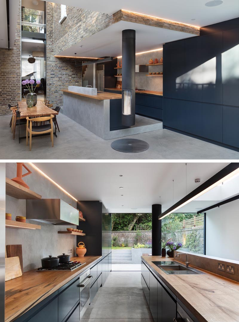 Designed with entertaining in mind, this modern house extension allowed for the creation of a living space, dining area, and a slightly raised modern kitchen with dark cabinets, concrete floors, and a oak countertops. #DarkKitchen #WoodCountertop #ConcreteFloor #DarkCabinets #KitchenDesign