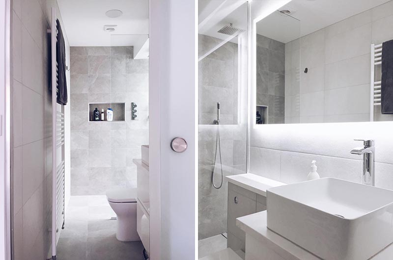 This modern en-suite bathroom features a walk-in shower with a built-in shower niche, and a backlit mirror is mounted above the vanity. #BacklitMirror #ModernBathroom #ShowerNiche