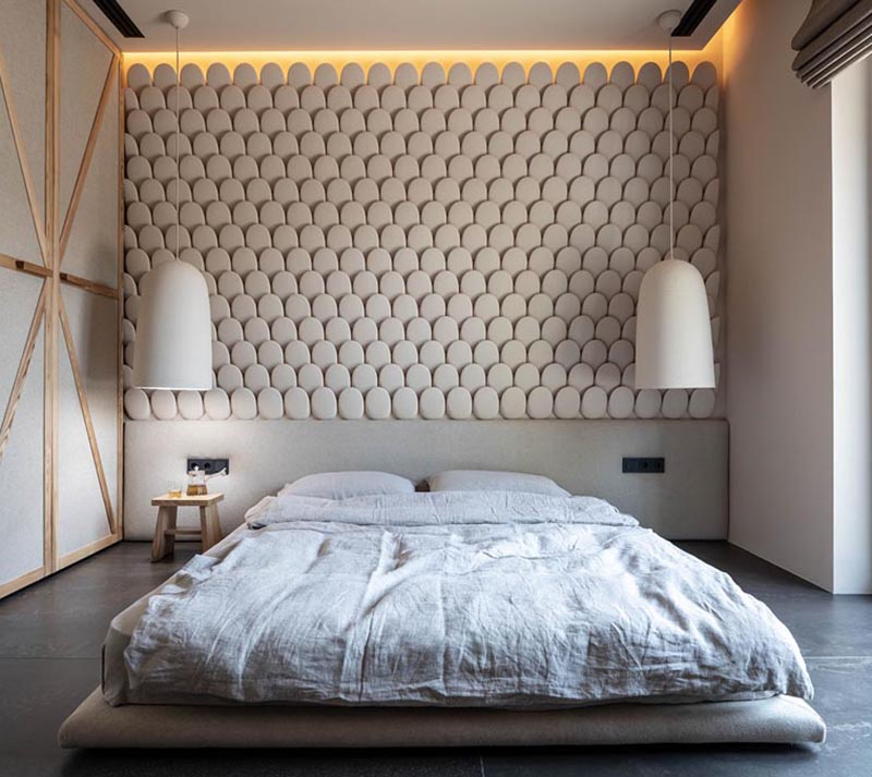 This modern bedroom features an eye-catching accent wall, that looks like small rounded stones, and helps to add texture to the room. #AccentWall #ModernBedroom #SculpturalWall #BedroomDesign