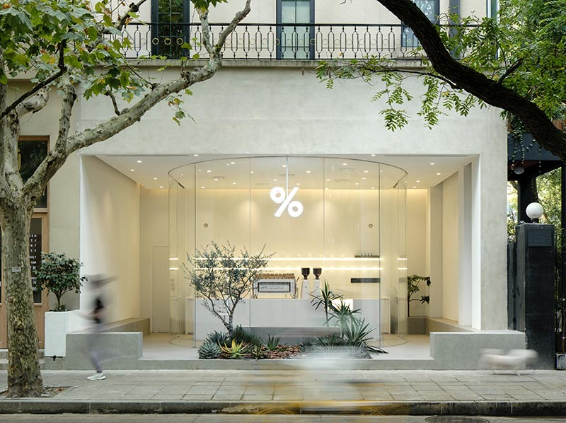 B.L.U.E. Architecture Studio has recently transformed a small 538 square foot (50 sqm) retail space into a modern and bright coffee shop in Shanghai, that features a curved glass facade. #ModernCoffeeShop #ModernCafe #CoffeeShop #Architecture #CafeDesign #CurvedGlass
