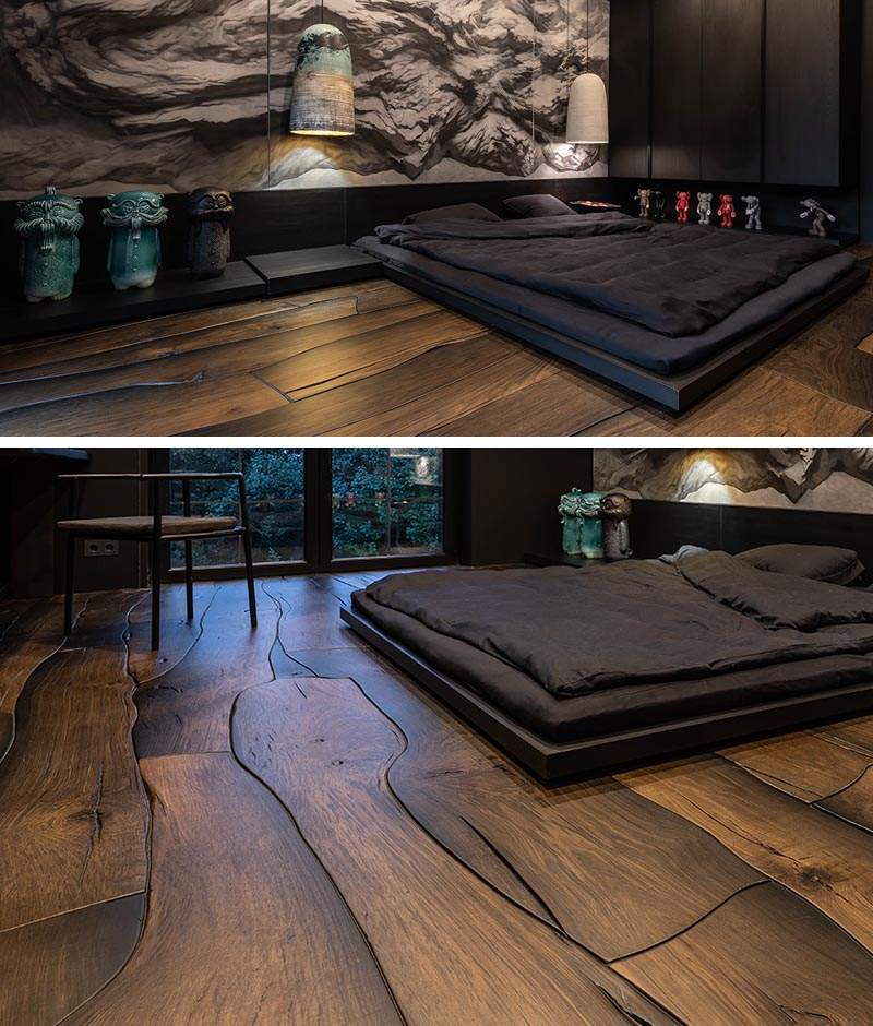 This modern and dramatic bedroom, inspired by the Japanese philosophy of wabi-sabi that finds beauty and harmony in imperfections, features a low tatami-style bed, that's positioned on the dark wood floor that looks like puzzle pieces that fit together. #ModernBedroom #WoodFloors #InteriorDesign #BedroomDesign #WallMural
