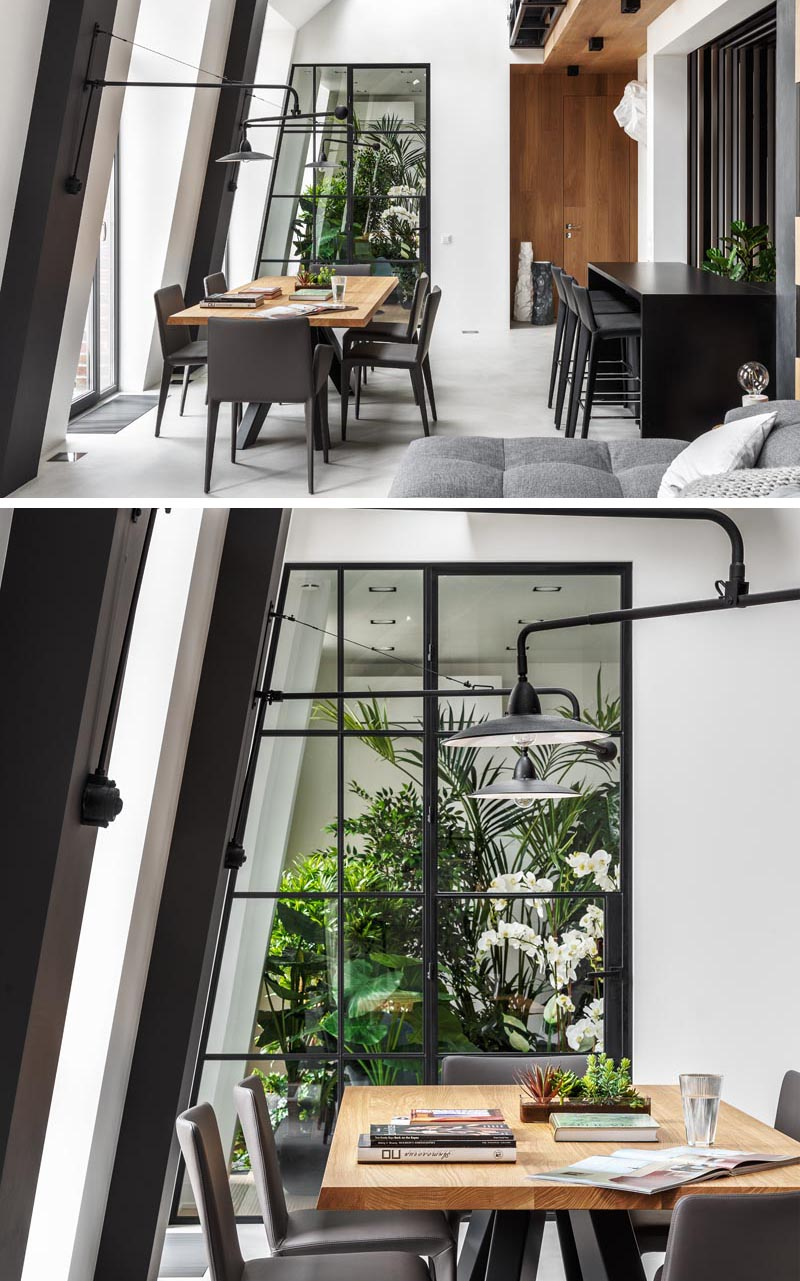 This modern apartment features an indoor plant room that can be seen through a black-framed glass wall, with a door that opens to reveal a quiet and peaceful sitting area. #IndoorGarden #IndoorPlantRoom #IndoorGardenRoom #ReadingNook #InteriorDesign