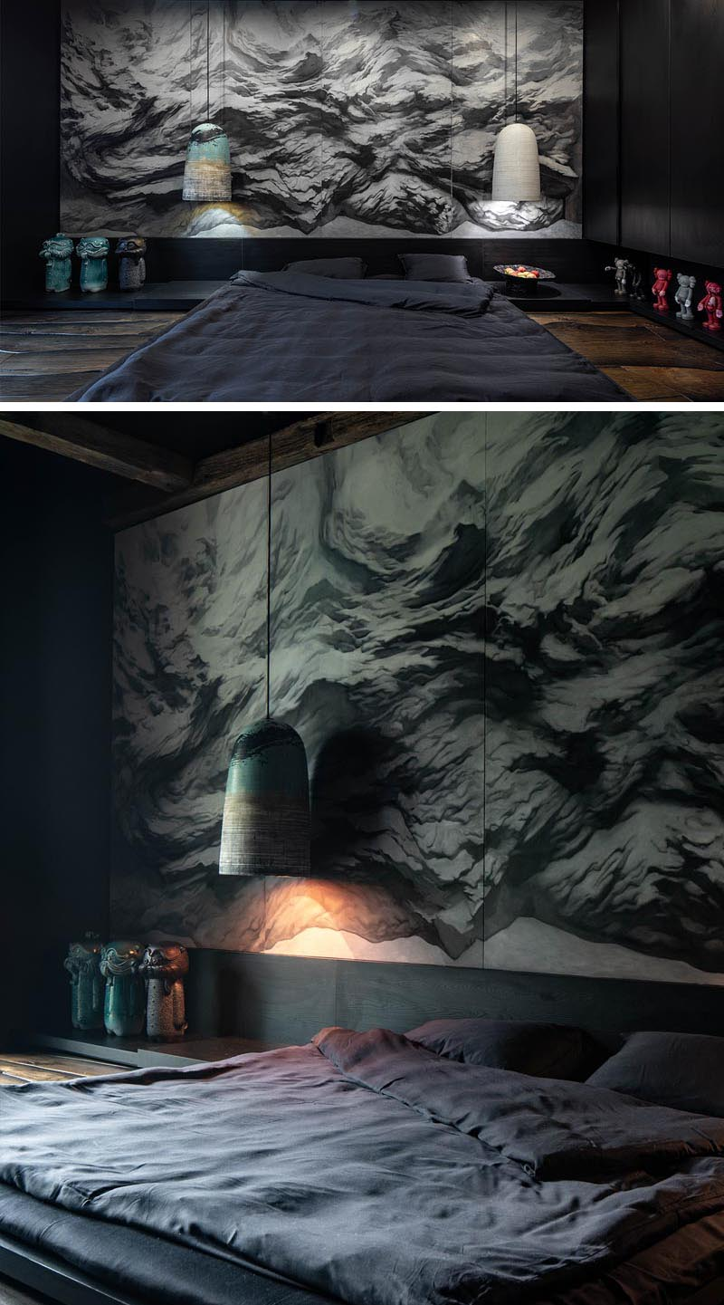 At the head of the bed in this modern and dramatic bedroom, is a large monochromatic Sumi-e-style (ink wash painting) that covers the wall and depicts distant landscapes. #MonochromaticMural #ModernArt #BedroomDesign #ModernBedroom #WallMural