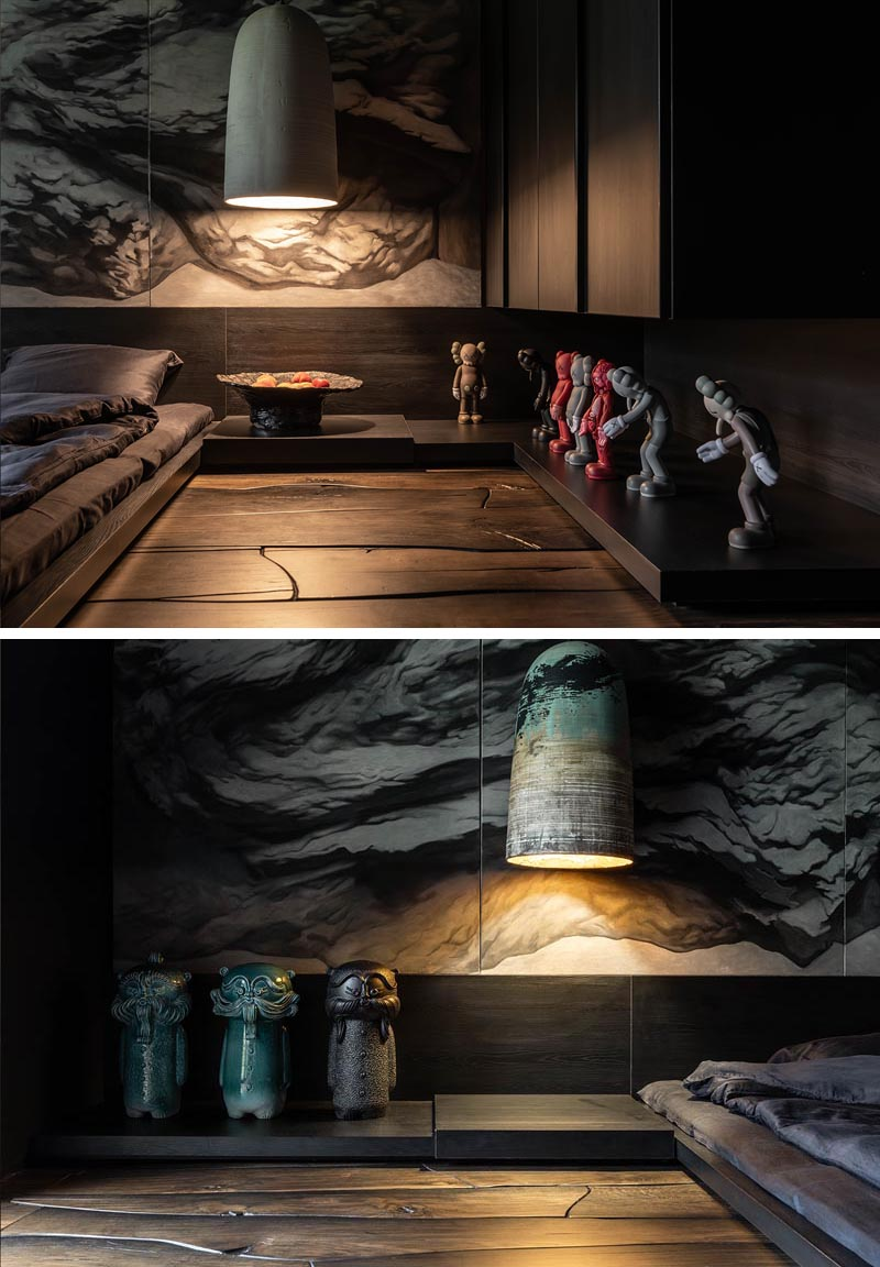 Low dark wood shelves lie below oversized pendant lights, and wrap around this modern bedroom. The shelves provide a place to showcase Kaws sculptures and ceramic art-toys named DIDO, that were also created by Sergey Makhno. #ModernBedroom #MasculineBedroom #DarkBedroom #MoodyBedroom