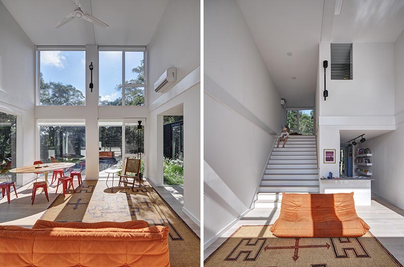 As shipping containers are quite narrow, the architects of this modern house opted to stack the containers, carving out the interior floor/wall/ceiling to create a large open living space and kitchen with stairs that lead up to a lofted bedroom. By finishing the interior white, it makes the all of the interiors feel brighter and larger. #ShippingContainerHouse #DoubleHeightLivingRoom #Stairs #LivingRoom #ShippingContainer