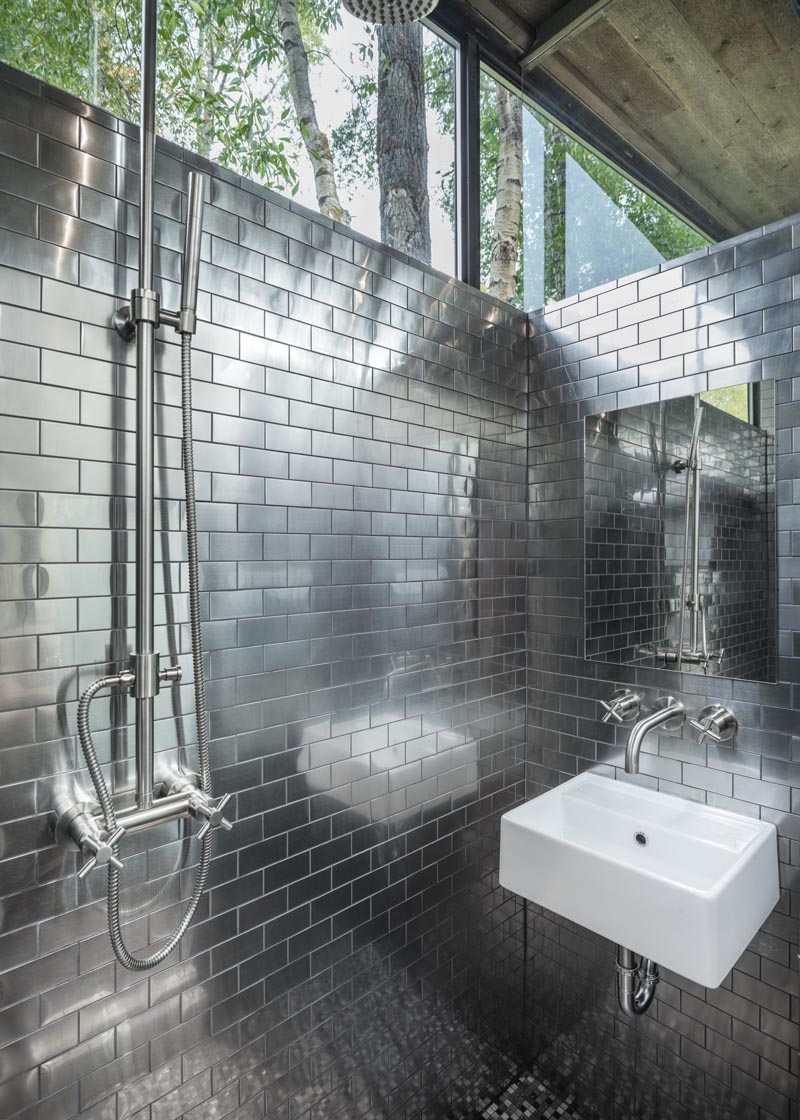 This tiny house has a full-size bathroom with stainless steel subway tiles that cover the walls, and windows that meet the roof. #Bathroom #TinyHouseBathroom #TinyHouse #StainlessSteelTiles