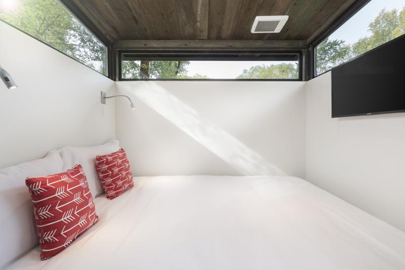 Long narrow windows wrap around the bedroom in this tiny house, while a pair of sconces provide light at night. #TinyHouse #TinyHome #Bedroom