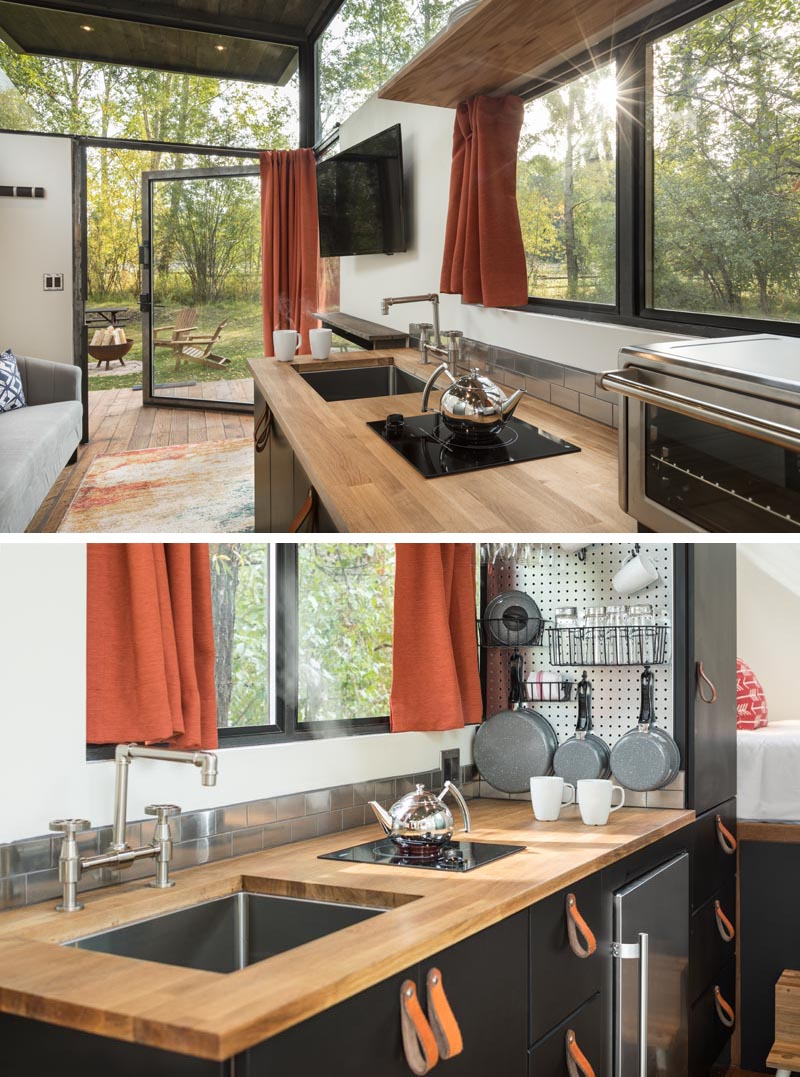 Adjacent to the living room of this tiny house is the kitchen, that has a wood countertop and leather pulls. #LeatherPulls #TinyHouse #TinyHouseKitchen #SmallKitchen