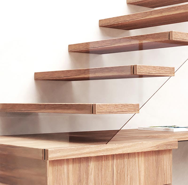 Here's a closer look that shows how the glass safety railing has been incorporated into the design of these modern wood stairs. By attaching the glass to the end of the stair treads, they are able to have it follow the shape of the stairs that makes it almost disappear, creating the sense of floating stairs. #ModernWoodStairs #GlassSafetyRailing #StairDesign