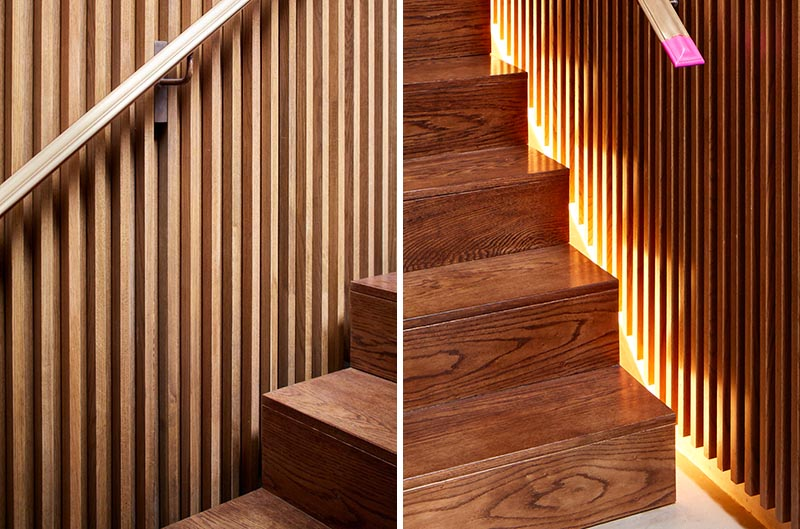 This modern house has a staircase with wood slat walls, handrails on both sides, and hidden lighting. #StairDesign #WoodStairs #StairLighting #HiddenStairLighting #StairHandrails