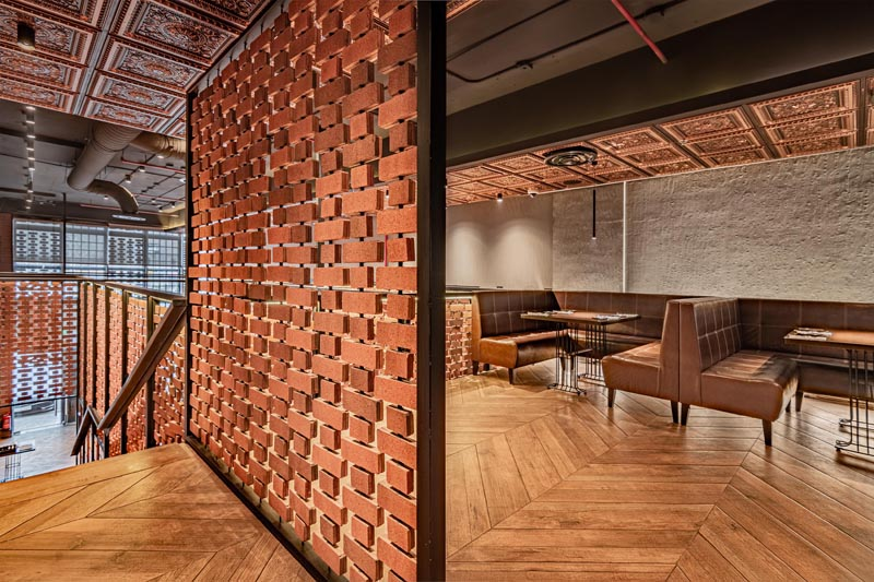 Open brick walls wrap around the different areas of this restaurant, like above the kitchen and along the stairs. They provide visiual interest and a sense of privacy on the upper level of the interior, without blocking the light. #RestaurantDesign #BrickWalls #ScreenIdea #BrickScreen