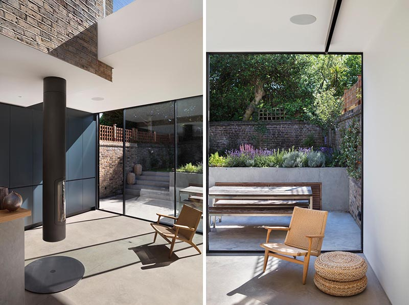This modern glass house extension features a pivoting fireplace, while floor-to-ceiling sliding doors provide access to the patio and raised secluded garden. #PivotingFireplace #FireplaceIdeas #Patio #Garden #SlidingDoors