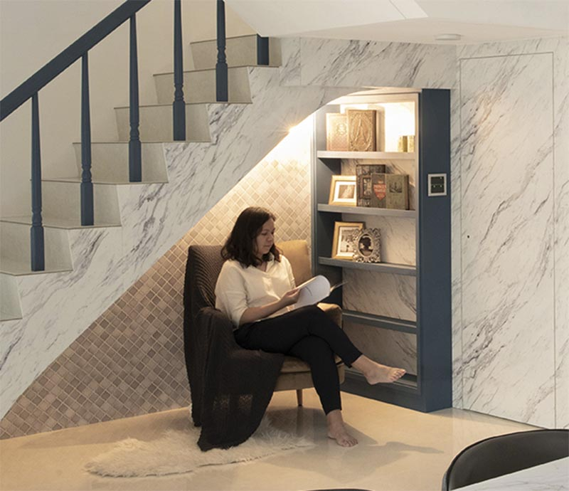 This modern house has a small reading nook under the stairs. It features a grey tile accent wall, a custom blue bookshelf, a comfortable armchair, a sconce, and a pair of outlets. #ReadingNook #SeatingNook #UnderStairNook #HomeLibrary