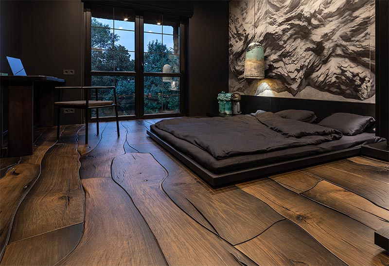 This modern bedroom features a unique wood floor made from 500-year-old oak, that fits together like puzzle pieces and showcases the natural grain, cracks, and knots.
