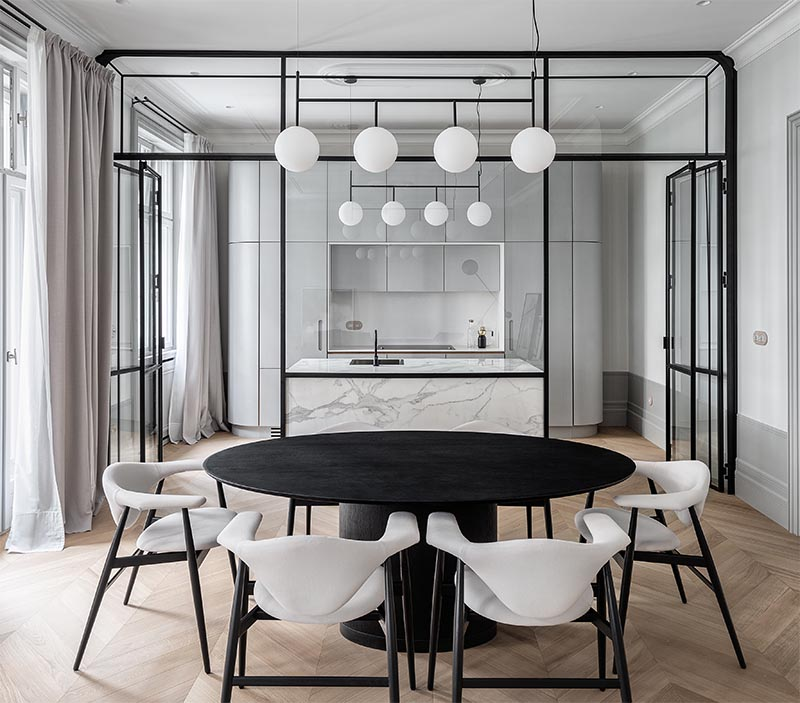 A Black Framed Gl Wall Separates The Kitchen From Dining