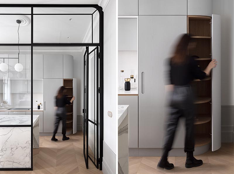 A Black Framed Glass Wall Separates The Kitchen From The Dining Room In This Apartment