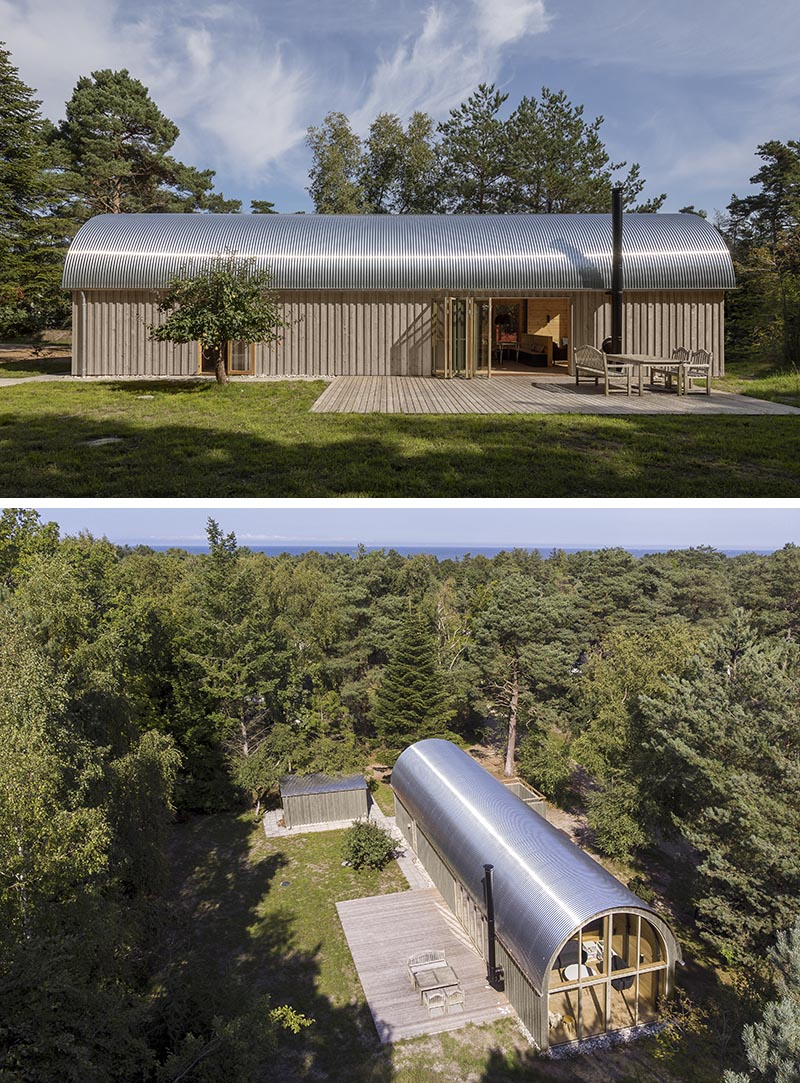 Valbæk Brørup Architects has designed a modern summer house that features a corrugated metal roof and a warm wood interior with a vaulted ceiling. #CorrugatedMetalRoof #MetalRoof #CurvedRoof #ModernArchitecture #ModernHouse