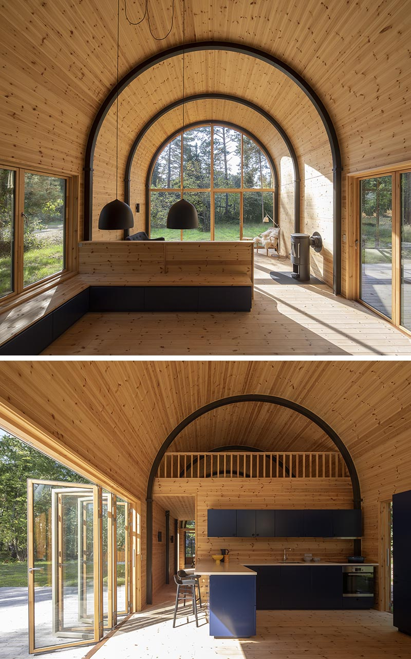 Inside this modern house with a curved vaulted ceiling, there's 8 eye-catching arched steel beams that provide the support for the structure, and at the same time, they create a strong contrast to the minimalist pine wood interior. #CurvedCeiling #VaultedCeiling #PineInterior #WoodInterior #ArchedBeams #SteelBeams #ModernHouse