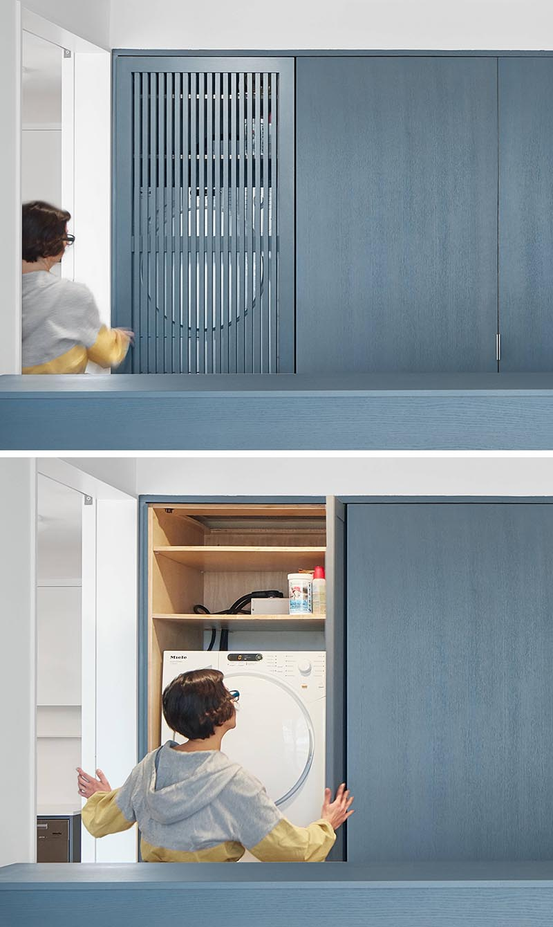 In this modern bedroom, a wall of matte-blue-grey stained closets has one with a wood slat door, which when opened tucks away to the side and reveals a laundry area with a washer / dryer and shelving above. #SmallLaundry #SmallSpaceIdeas #LaundryIdeas #ClosetIdeas