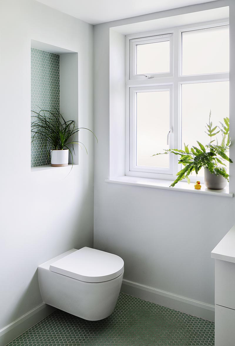 This modern bathroom features a recessed shelf, which is large enough to display a plant, and includes small hexagon penny tiles with white grout. It also helps to add a pop of color to the plain grey wall, and draws attention away from the toilet below. #BathroomShelf #BathroomIdeas #RecessedShelf #PennyTile #BathroomDesign