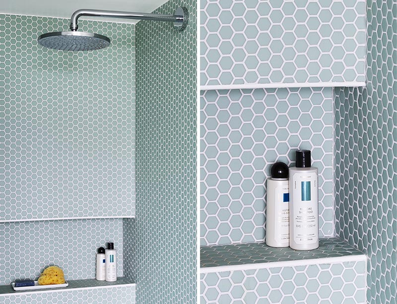 This modern bathroom features a shower lined with light blue hexagon penny tile, and also has a built-in shower niche. #ShowerNiche #PennyTile #ShowerIdeas #BathroomIdeas