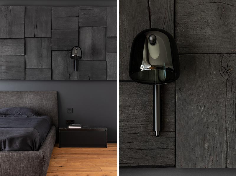 In this modern black bedroom, there's a black wall that provides a backdrop for the matching bed, while a blackened wood panel accent wall adds interest and texture to the room. #BlackBedroom #BlackAccentWall #BlackWoodAccentWall #WoodAccentWall #ModernBedroom
