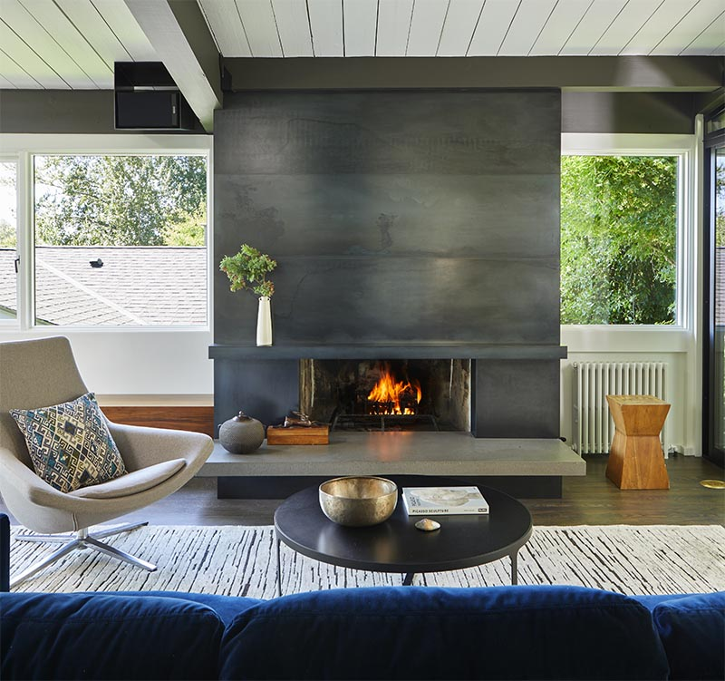 A Blackened Steel Fireplace Surround With A Concrete ...