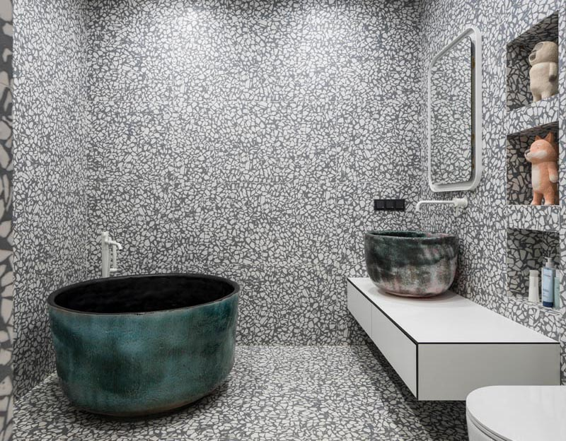 A grey and white large aggregate terrazzo tile has been installed in this modern bathroom, covering the walls and floor. #GreyAndWhiteBathroom #GreyBathroom #BathroomIdeas #SoakingTub #ShelvingNiche #ModernBathroom