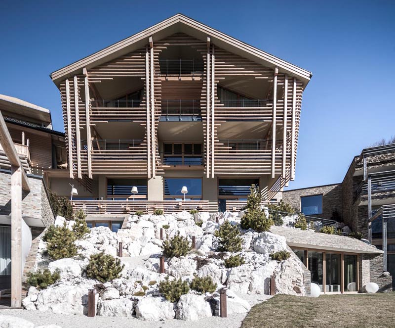 noa* network of architecture designed the renovation of Valentinerhof, a hotel in Italy, that showcases an exterior of smooth round logs. #ModernLogExterior #LogFacade #WoodFacade #HotelDesign