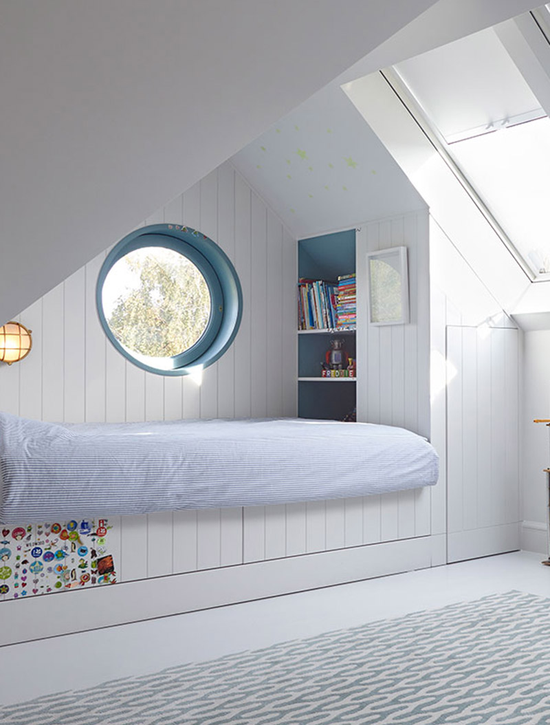 This modern kids bedroom has a built-it bed that's been tucked into one end of the room, creating an open play area that's softened by the use of a modern rug, and includes storage in the form of a closet and bookshelf. #KidsBedroom #ModernKidsBed #BuiltInBed #Interiors #BedroomDesign