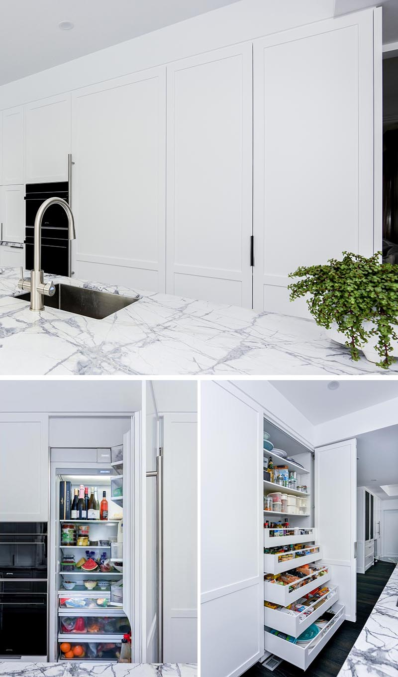This modern grey and white kitchen as an integrated fridge and a pantry cupboard. To make the most of the available space, the pantry has wide but shallow pull-out drawers that allow for the easy storage of a variety of items. #PantryIdeas #IntegratedFridge #ModernKitchen #KitchenIdeas #KitchenStorage #KitchenOrganization