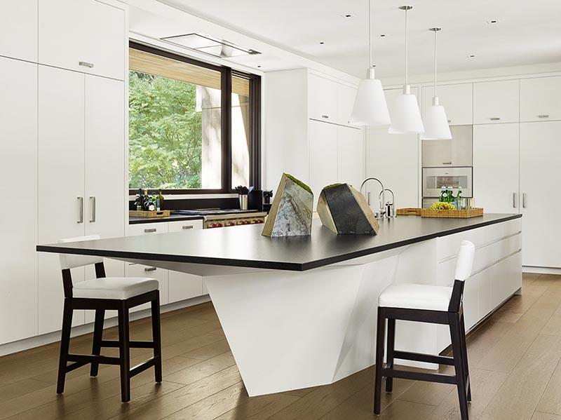 A modern geometric white kitchen island with a black countertop.