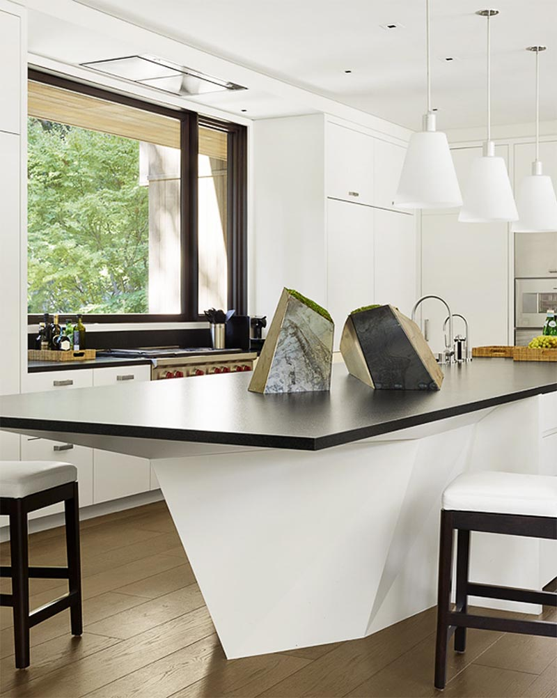 A geometric kitchen island that features a black countertop.