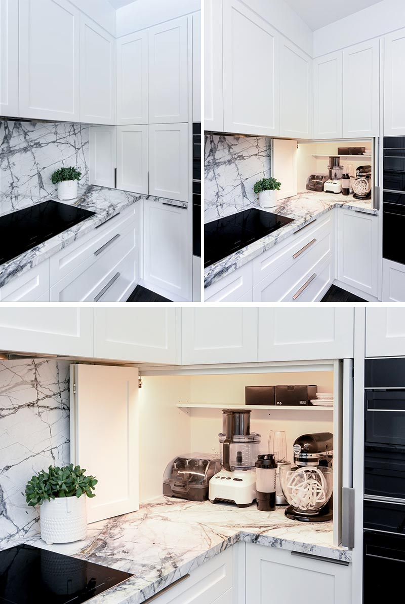 Tucked into the corner of this modern grey and white kitchen is an appliance garage that stores blenders and mixers. An interior light makes it easy to see the items within the cabinet. #KitchenDesign #KitchenIdeas #KitchenStorage #KitchenOrganization #ApplianceGarage