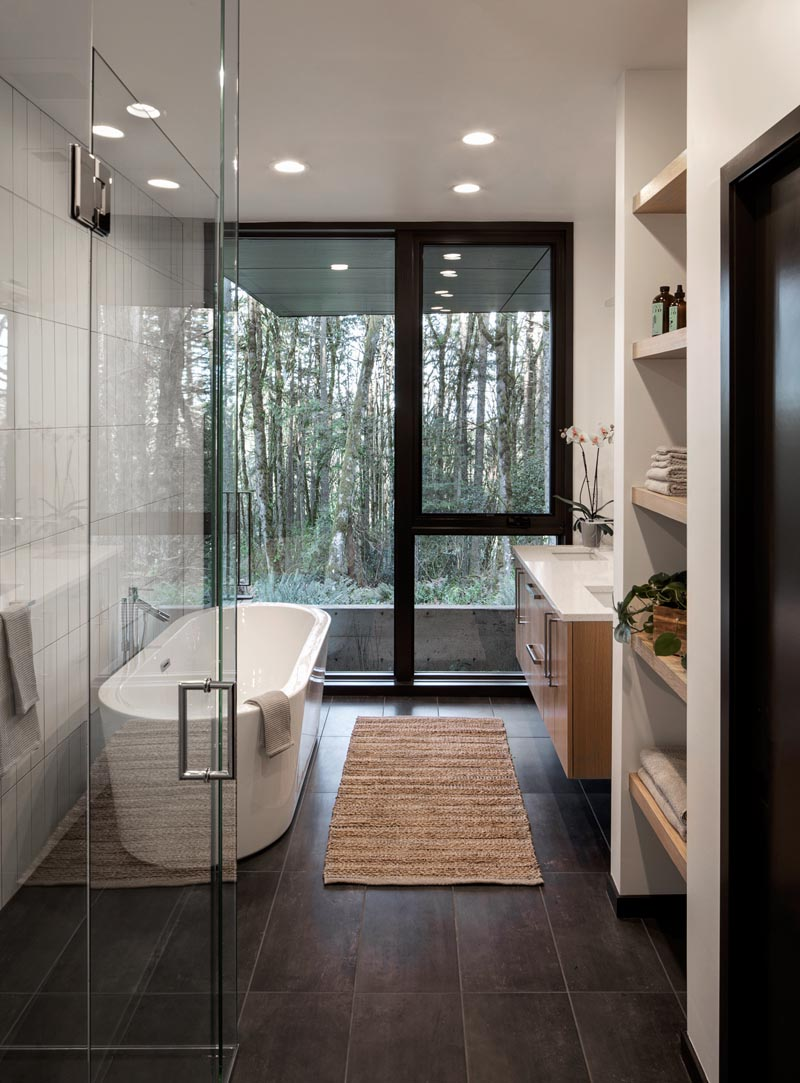 In this modern master bathroom, a freestanding bathtub and the shower are positioned against one wall, while a floating wood vanity with dual sinks and a wall of open shelving are located on the opposite wall. #MasterBathroom #ModernBathroom #BathroomIdeas