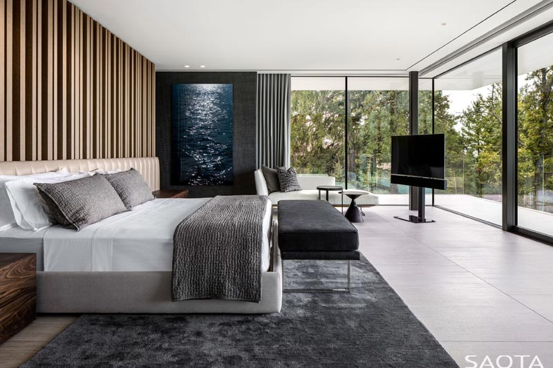 In this modern master bedroom, walls of glass provide plenty of natural light, and when privacy is needed, grey curtains that match the contemporary rug can be drawn. #MasterBedroom #GlassWalls #GreyCurtains