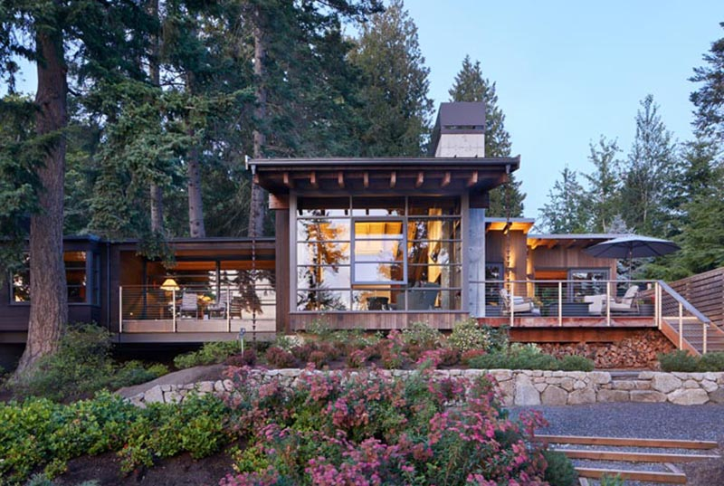 This modern house has deep overhanging eaves with exposed cedar rafters, offering protection from the weather and connecting to rain chains, aiding with the flow of rainwater into the garden. #OverhangingEaves #DeepEaves #ModernArchitecture #ExposedRafters#CedarRafters #HouseDesign #PacificNorthwest