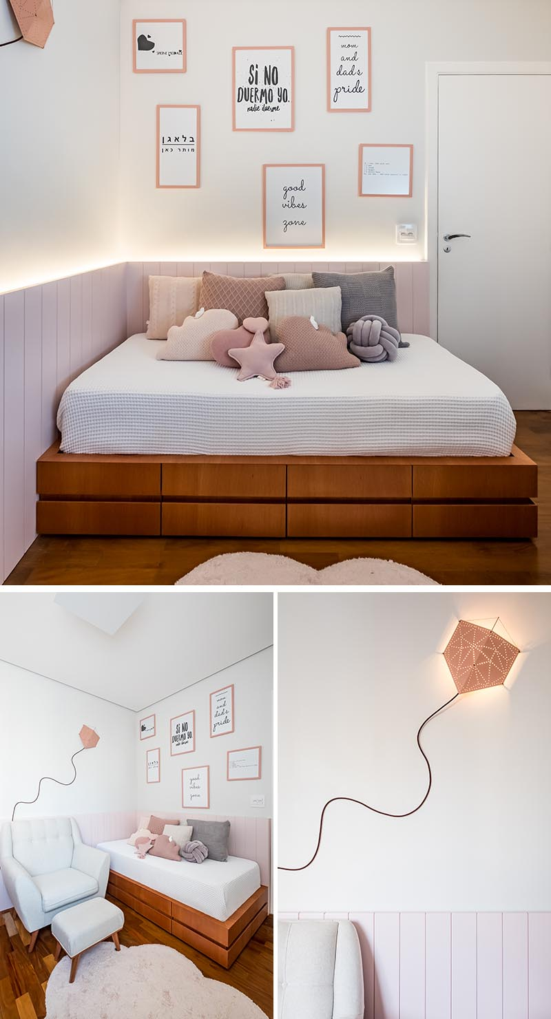 A palette of soft pinks and natural Jequitibá wood have been used throughout this modern nursery, while wood paneling with hidden indirect lighting helps to create a sense of warmth. Upon entering the nursery, there's a custom-designed day bed with storage drawers below it, and a kite lamp on the wall adds a creative and playful touch. #ModernNursery #PinkNursery #GirlsBedroom #InteriorDesign #Interiors #NurseryRoom #BabyRoom