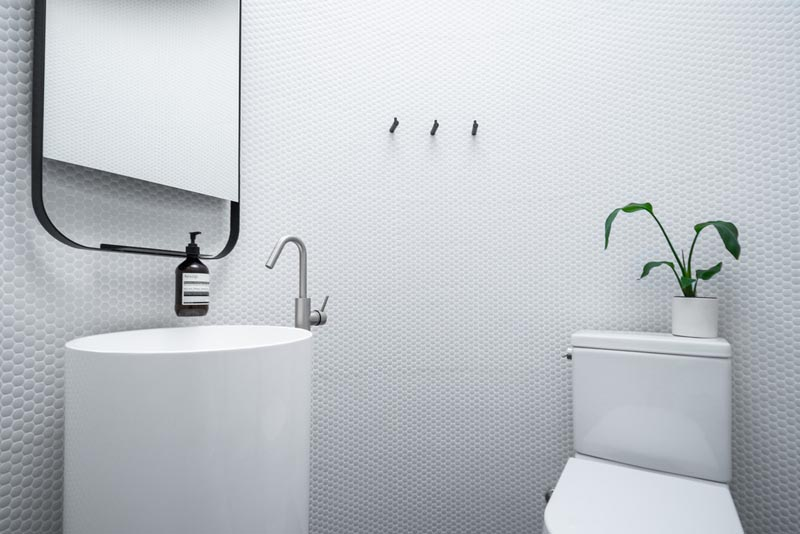 This modern circular bathroom has walls of white penny tiles, a curved pedestal vanity with a rounded edge mirror, and a toilet. #Bathroom #RoundBathroom #PennyTiles #PedestalVanity