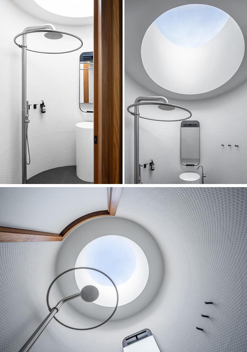 This modern circular bathroom has walls of white penny tiles, and a round skylight above the shower that reflects the overall shape of the bathroom. #RoundSkylight #CircularSkylight #Bathroom #RoundBathroom #PennyTiles