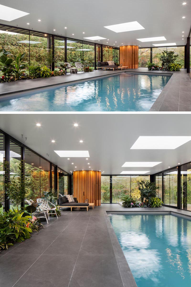 Inside this modern pool house, there's skylights that scatter the ceiling, a deck with designated places for lounging, and planters filled with lush tropical plants of varying heights. #PoolHouse #Planters #BuiltInPlanters #SwimmingPool